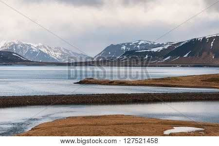 Amazing Icelandic Landscape with lake dramatic sky and mountains covered in snow on the background