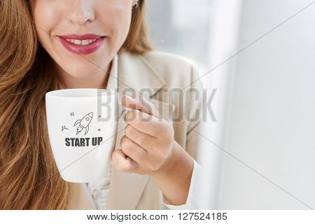 Cropped image of smiling business lady drinking coffee with start-up inscription