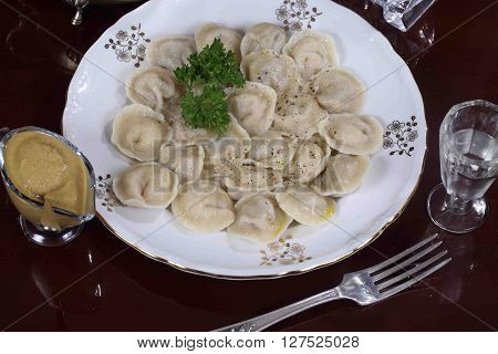 dumplings with sour cream ground pepper and vodka in a decanter