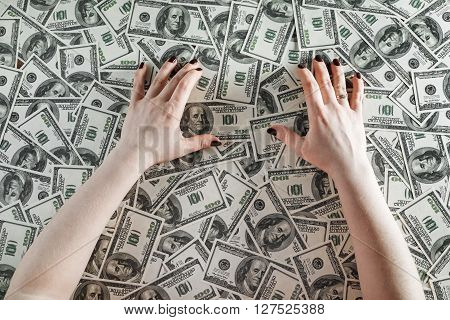 Female hands on a background of money. Hands and money. Many one hundred dollar bills. Fake money. Business concept. Top view.