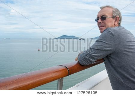 Middle aged man on ship looking out contemplating