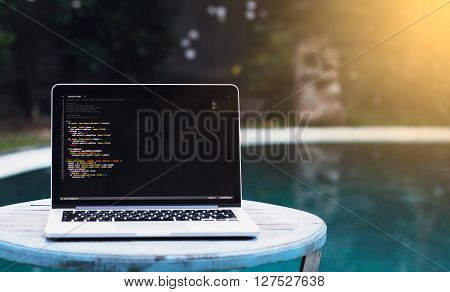 laptop on a wooden table against the background of accepted Swimming pool