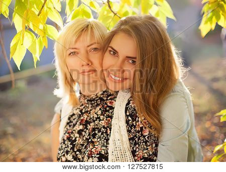 Close up portrait of mother and daughter hugging. Beautiful mother and her adult daughter.
