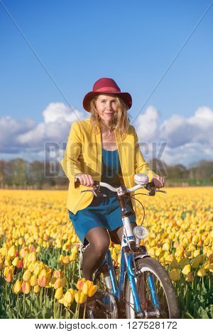 Cheerful female riding her bike through sunny tulip fields