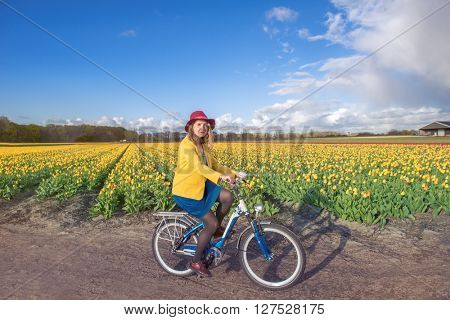 Woman in hat cycling along typical Dutch spring tulip fields