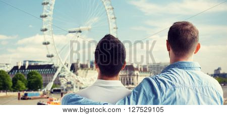 people, homosexuality, same-sex marriage, travel and love concept - close up of happy male gay couple hugging from back over ferry wheel background