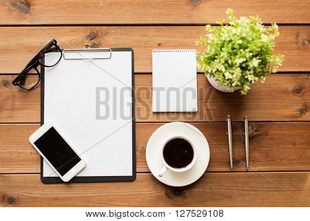 business and technology concept - close up of smartphone, clipboard, coffee cup, eyeglasses and notepad on wooden table
