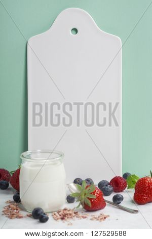 White ceramic serving board, yogurt and berry over light blue background, space for your text