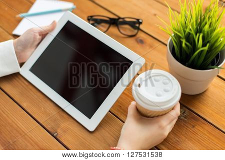 business, education, technology, people and advertisement concept - close up of woman with blank tablet pc computer screen drinking coffee on wooden table