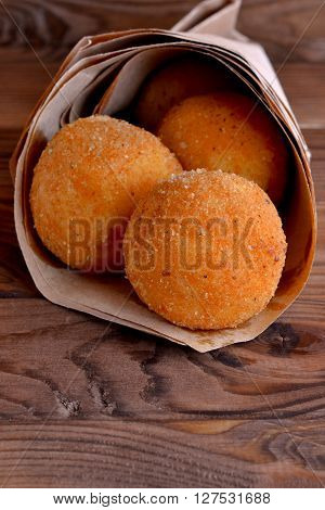 Arancini rice balls. Fried rice balls in paper on brown wooden background. Snack, street food. Close-up