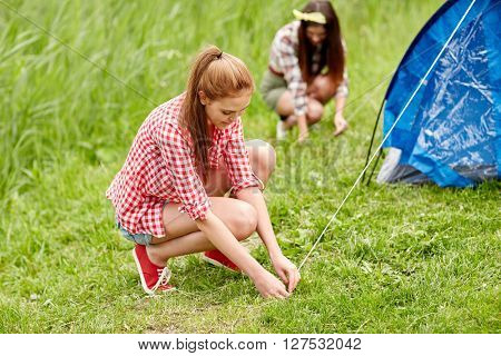 camping, travel, tourism, hike and people concept - smiling friends setting up tent outdoors