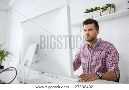 business, technology, education and people concept - young creative man or student with computer at office