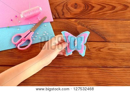 Children hand holding a felt butterfly. Felt sheets, scissors, thread, beads. Brown wooden background with copy space for text