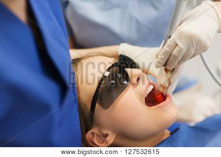 people, medicine, stomatology and health care concept - female dentists with dental curing light and mirror treating patient girl teeth at dental clinic office