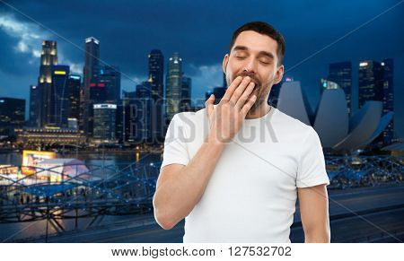 travel, tourism, bedtime and people concept - tired yawning man over night singapore city background