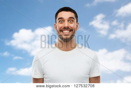 expression and people concept - man with funny face over blue sky and clouds background