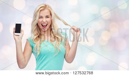 emotions, expressions, technology and people concept - smiling young woman or teenage girl showing blank smartphone screen and winking over holidays lights background