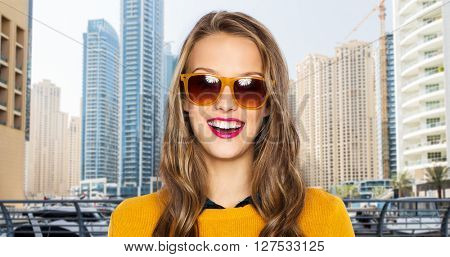 people, style and fashion concept - happy young woman or teen girl face in sunglasses over dubai city street background