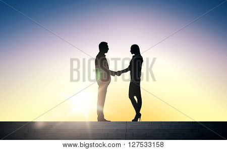 business, teamwork, partnership, cooperation and people concept - business people shaking hands standing on stairs over sun light background