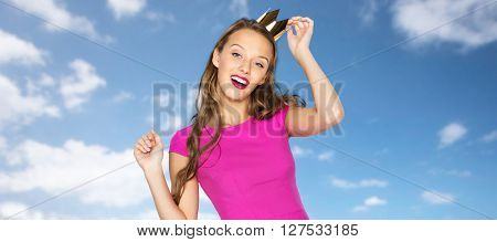 people, holidays and fashion concept - happy young woman or teen girl in pink dress and princess crown over blue sky and clouds background