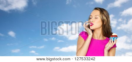 people, holidays, party, junk food and celebration concept - happy young woman in pink dress eating birthday cupcake over blue sky and clouds background