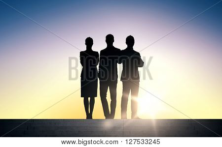 business, teamwork and people concept - business people silhouettes on stairs over sun light background