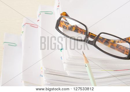 Pencil And Spectacles Put On Stack Of Overload Paper