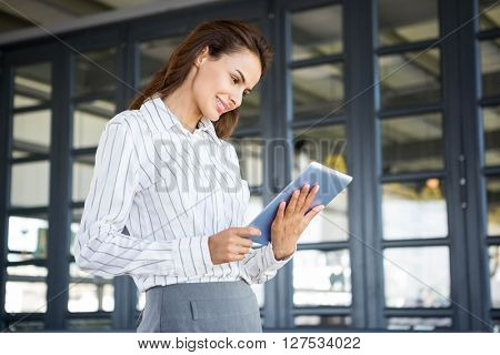 Portrait of young businesswoman holding digital document in office