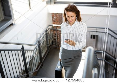 Businesswoman using phone and climbing staircase in office