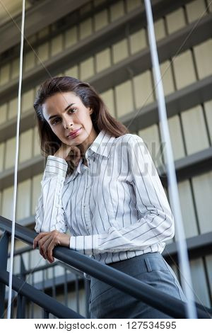 Portrait of businesswoman standing near a railing in office