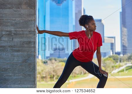 Runner girl stretching listening music earphones in the city