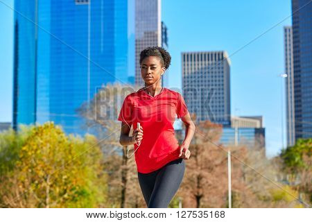 Runner girl running and listening music earphones in the city park