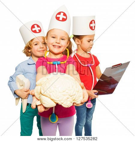 Picture of three little children wearing doctors cap, holding x-ray, tooth dummy and cerebrum model, isolated on white