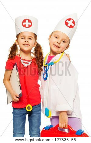 Close-up portrait of two beautiful little doctors playing with medical tools, isolated on white