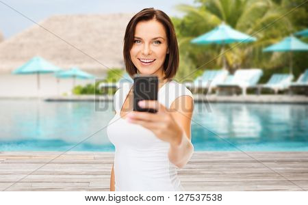 travel, tourism, summer vacation, technology and people - happy young woman taking selfie picture by smartphone over exotic hotel resort beach with swimming pool and sunbeds background