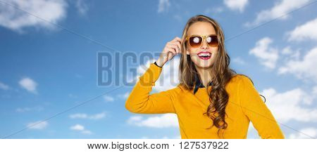 people, style and fashion concept - happy young woman or teen girl in casual clothes and sunglasses over blue sky and clouds background