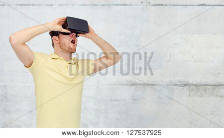 3d technology, virtual reality, entertainment and people concept - amazed young man with virtual reality headset or 3d glasses playing game over concrete gray wall background