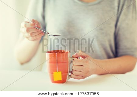 food, junk-food, drinks and unhealthy eating concept - close up of woman adding sugar to tea cup
