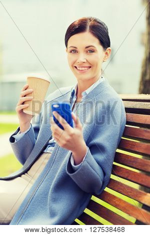 business and people concept - young smiling woman with smartphone sitting on bench and drinking coffee in city