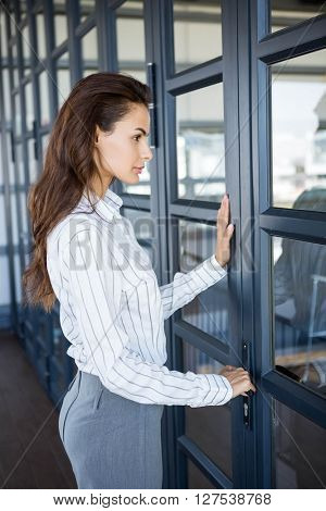 Young businesswoman opening office door