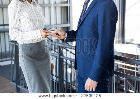 Businessman giving credit card to businesswoman in office