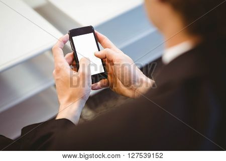 Close-up of businessman text messaging on smartphone