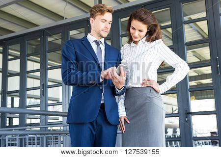 Businessman and businesswoman looking at smartphone in office