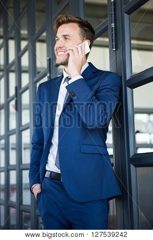 Businessman talking on smartphone in office