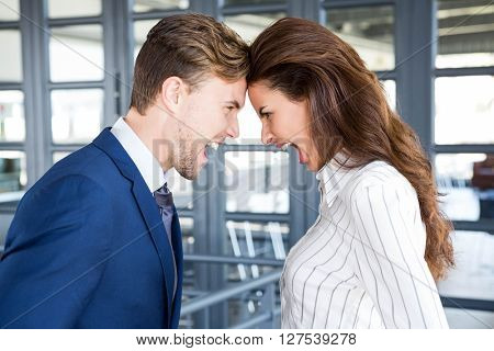 Close-up of angry businessman and businesswoman standing head to head