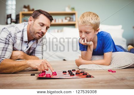 Close-up of father and son playing checker game while lying on floor at home