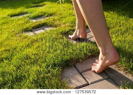 A girl goes on a path in a garden