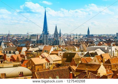 Aerial panoramic view of Ghent, Belgium with  roofs and traditional medieval buildings, church tower against cloudy blue sky