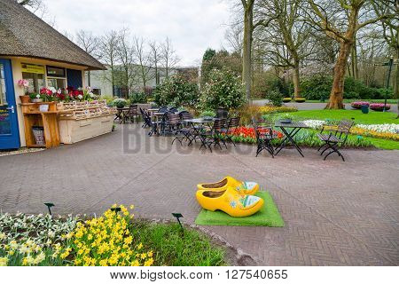 Lisse, Netherlands - April 4, 2016: Typical yellow dutch wooden clogs or klompen, painted with windmill and Keukenhof park view