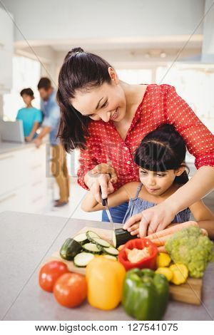Close-up of happy woman teaching daughter to cut vegetables at home